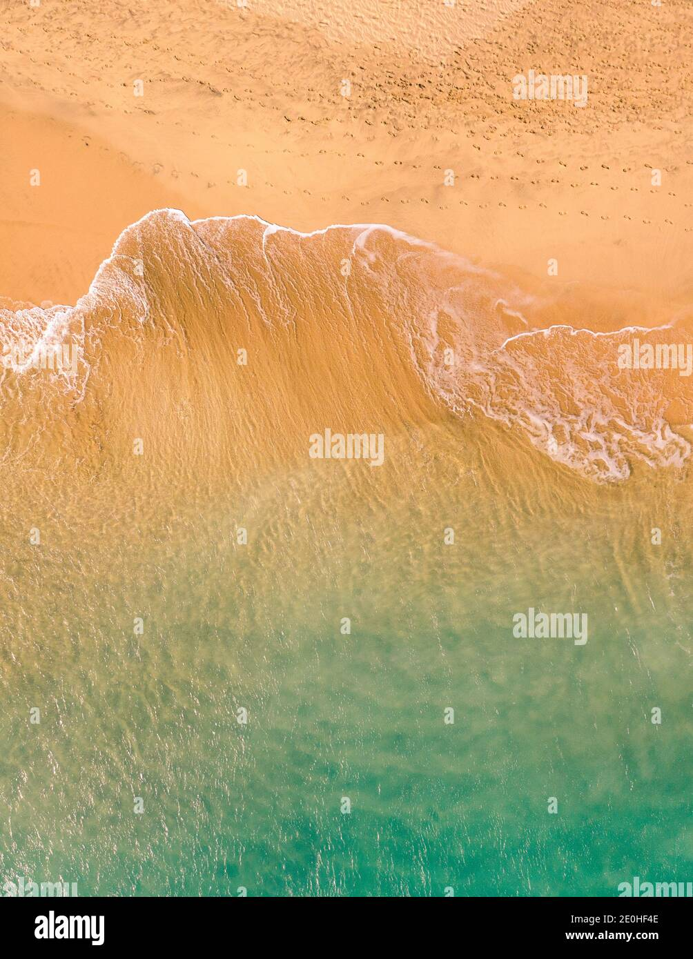 Aerial top down view of beautiful Atlantic ocean coast with crystal clear turquoise water and sandy beach, waves rolling into the shore Stock Photo