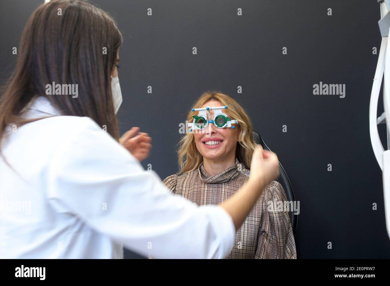 woman in an optician's having a visual exam and buying glasses. Stock Photo