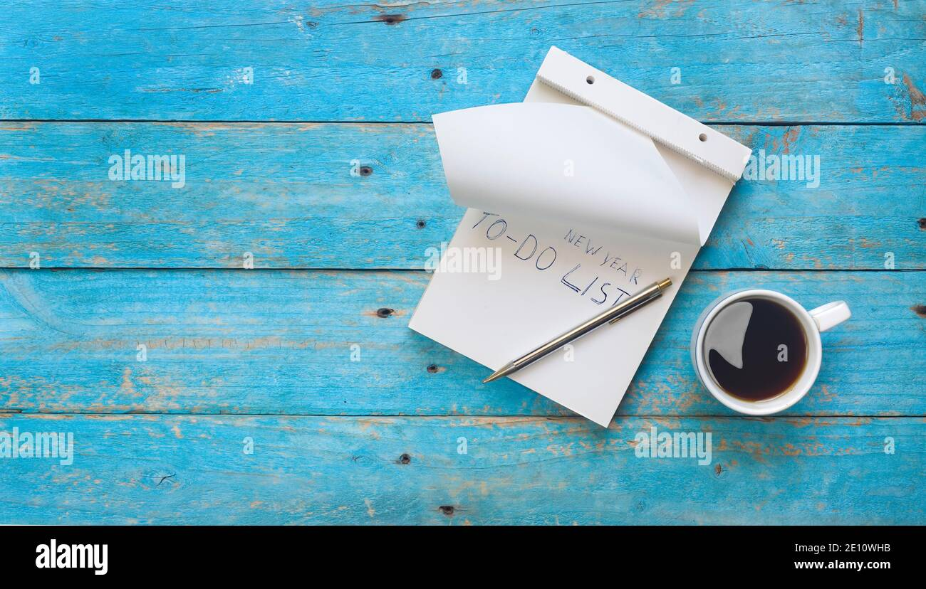 New Year's resolutions mock up with writing pad, text and cup of coffee, flat lay, free copy space Stock Photo