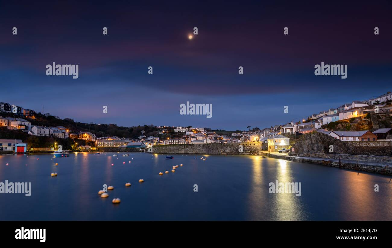 Moon setting behind Mevagissey harbour in Cornwall at sunrise Stock Photo