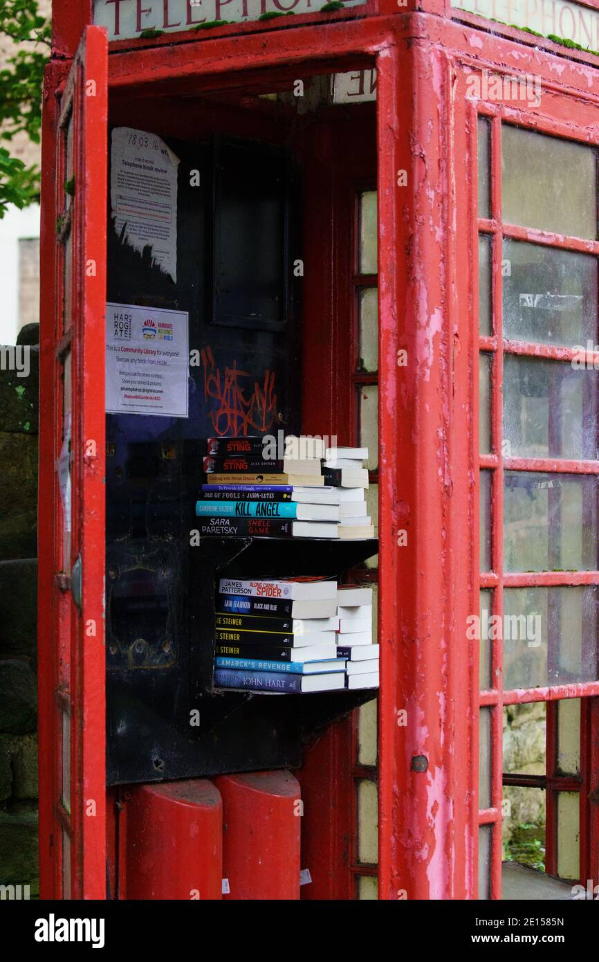 Old disused red telephone box made into a temporary community library for people to bring & borrow books, Valley Drive, Harrogate, North Yorkshire, UK. Stock Photo