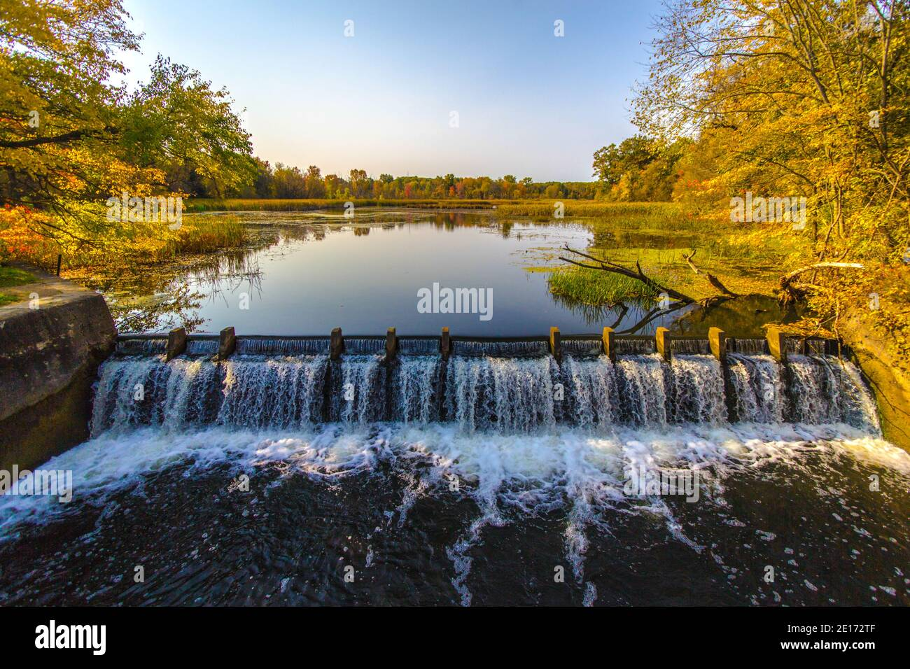 Dam on river creates a beautiful natural wetland with trees reflected in the reservoir. Stock Photo
