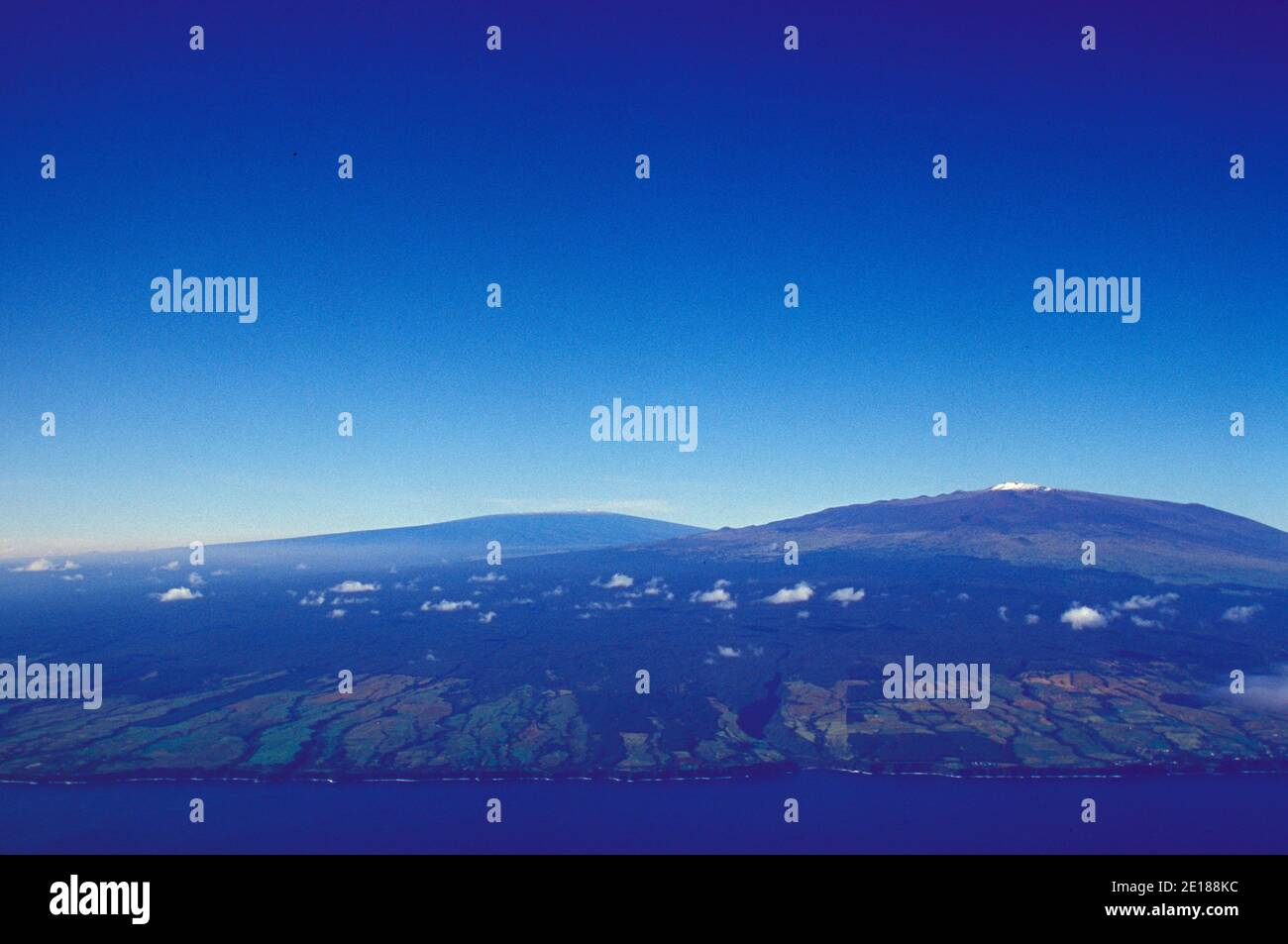 Aerial view of snow capped Mauna Kea with observatories, and Mauna Loa in background. Stock Photo