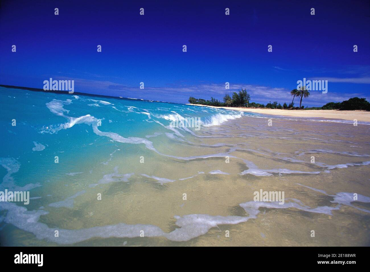 Waves breaking in clear blue water on white sand beach, Velzyland, North Shore, Oahu Stock Photo