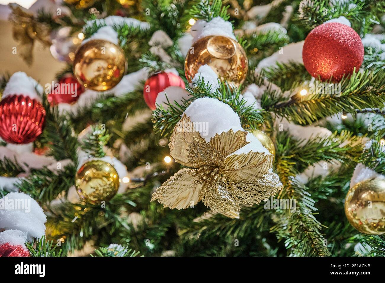 Beautiful Gold And Red Christmas Decorations On An Artificial Christmas Tree Sprinkled With Snow Close Up Stock Photo Alamy