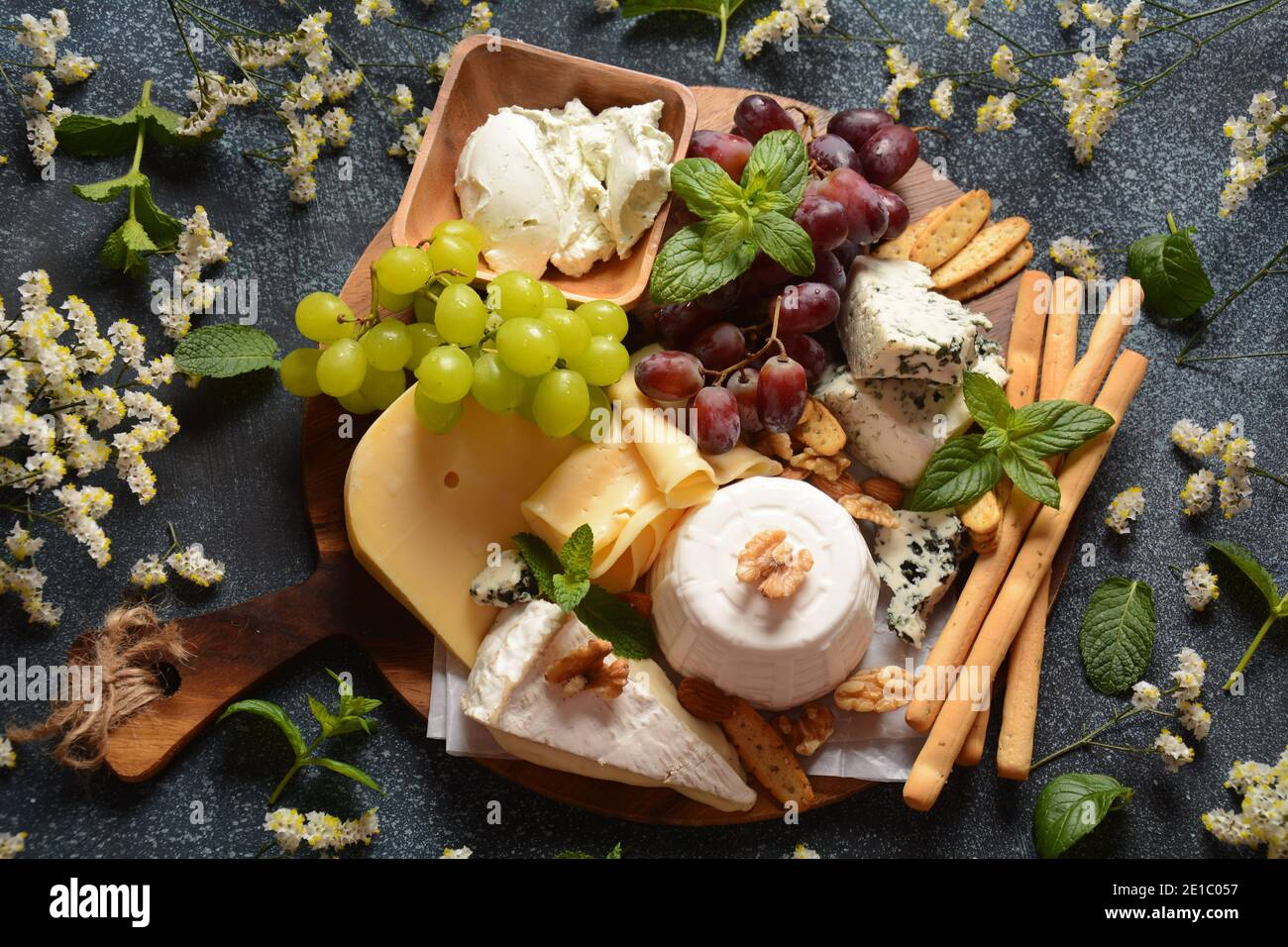 Cheese platter with assorted cheeses, grapes, nuts and snacks . Italian, French cheese starter. Traditional Shavuot Jewish Holiday food concept Stock Photo
