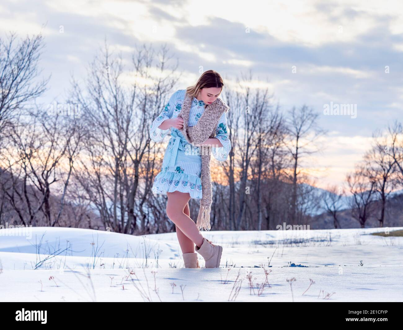 Young woman in Winter standing on snow-covered field looking bending down along long scarf Stock Photo