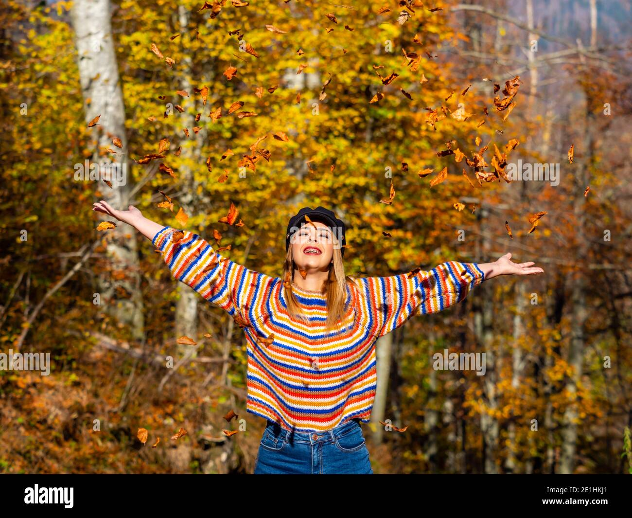 Autumnal warm light and young woman in nature Green-Yellow forest countryside country throwing leaves upwards up happiness happy smiling positive Stock Photo