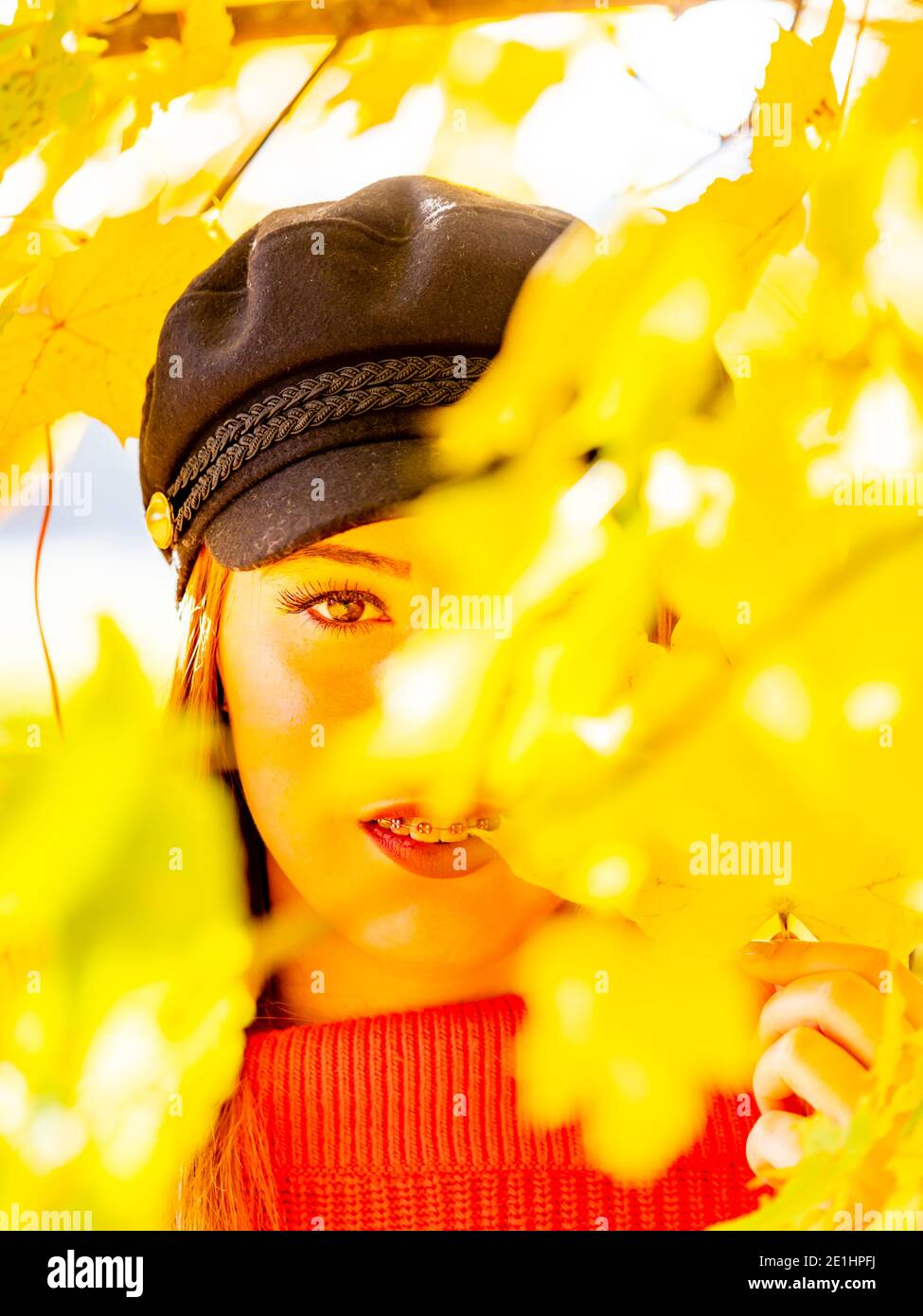 Autumnal warm light and young woman in nature bright Yellow forest countryside country portrait looking peeking peek at camera between leaves branches Stock Photo