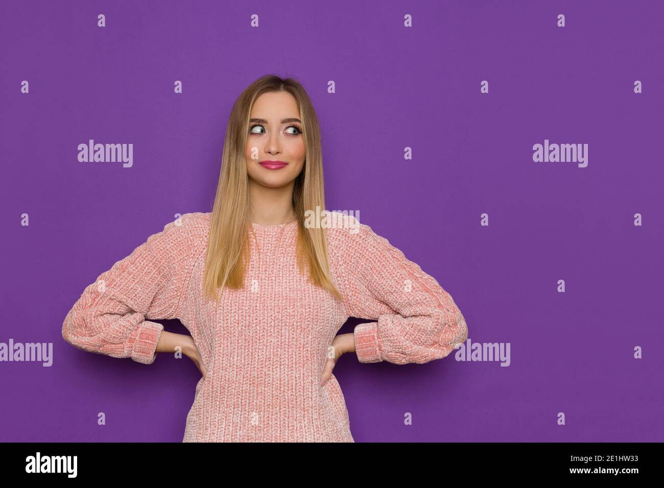 Cute young woman in pink sweater is posing with hands on hip and looking at the side. Waist up studio shot on purple background. Stock Photo