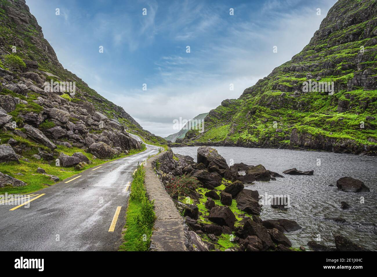 Narrow winding road running alongside lake and stream in green valley, Gap of Dunloe in Black Valley, Ring of Kerry, County Kerry, Ireland Stock Photo