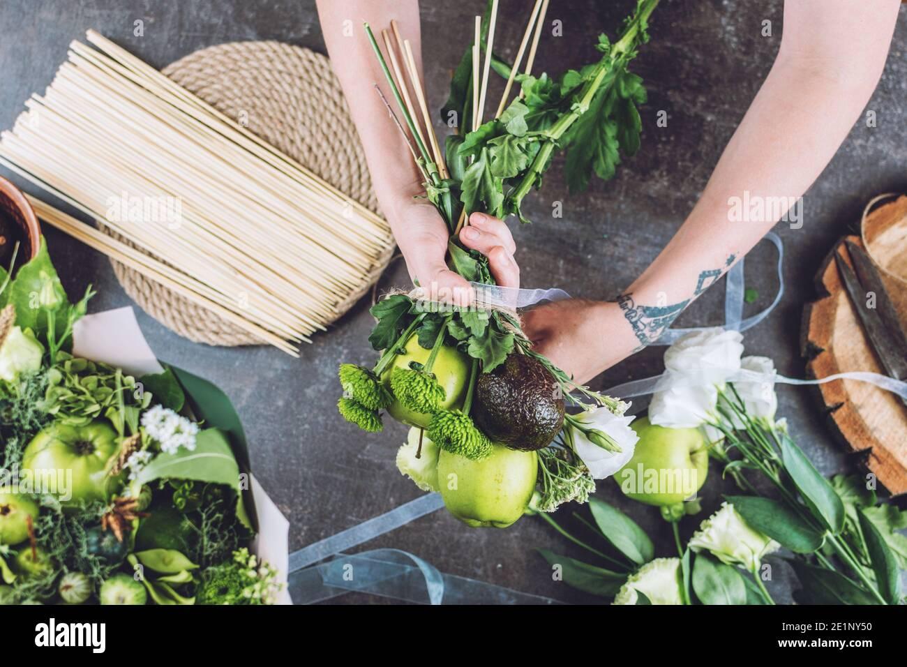 Hobbies and activities, arts and crafts during coronavirus. Florist woman make fruit edible bouquet. Naturalness, Flower Arranging, florist tricks Stock Photo