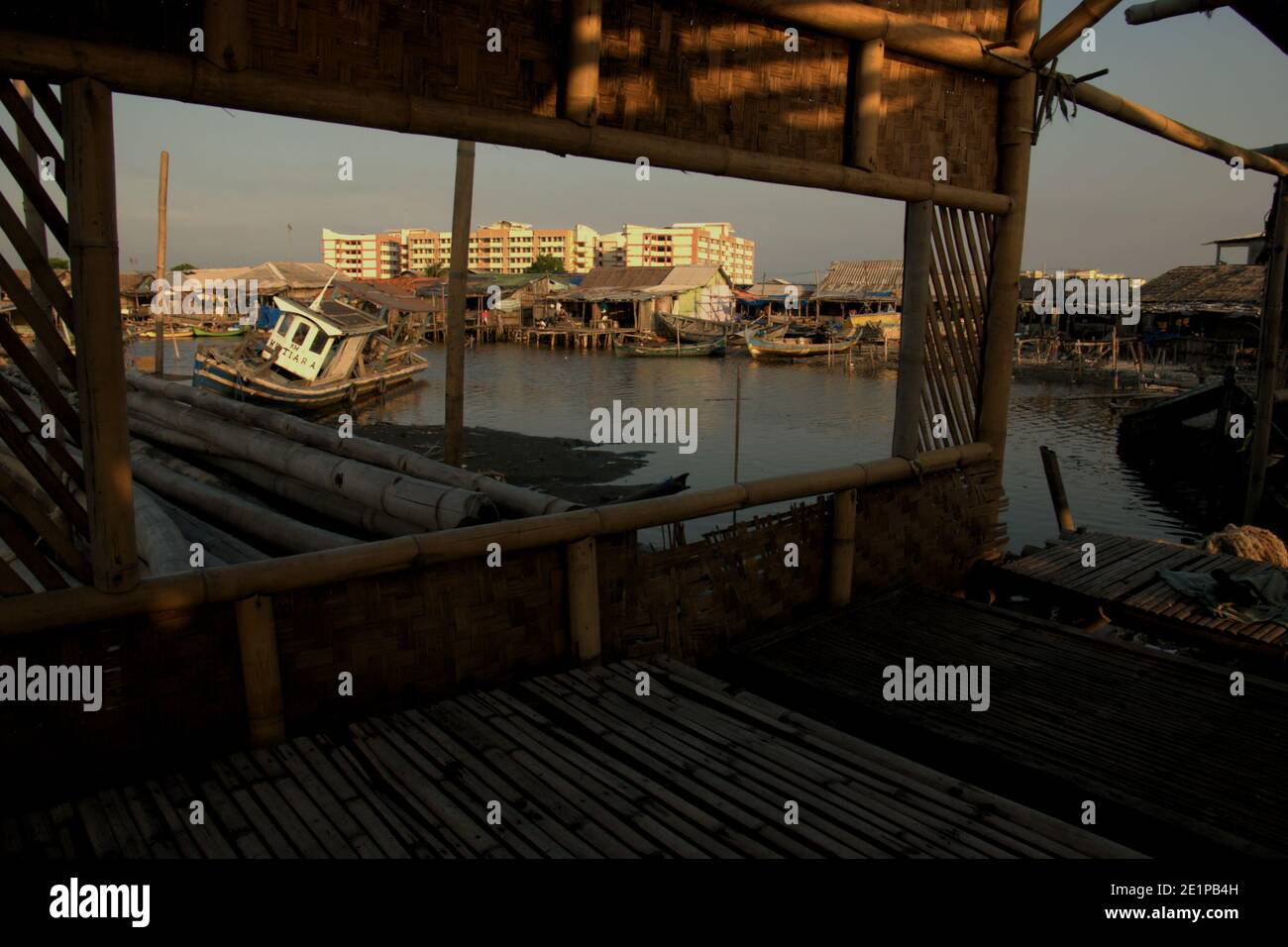 Fishing boats on intertidal area, fishing village and newly built flat building seen from inside an abandoned sea food restaurant in Marunda village in the coastal area of Jakarta, Indonesia. Archival photo (2008). Stock Photo