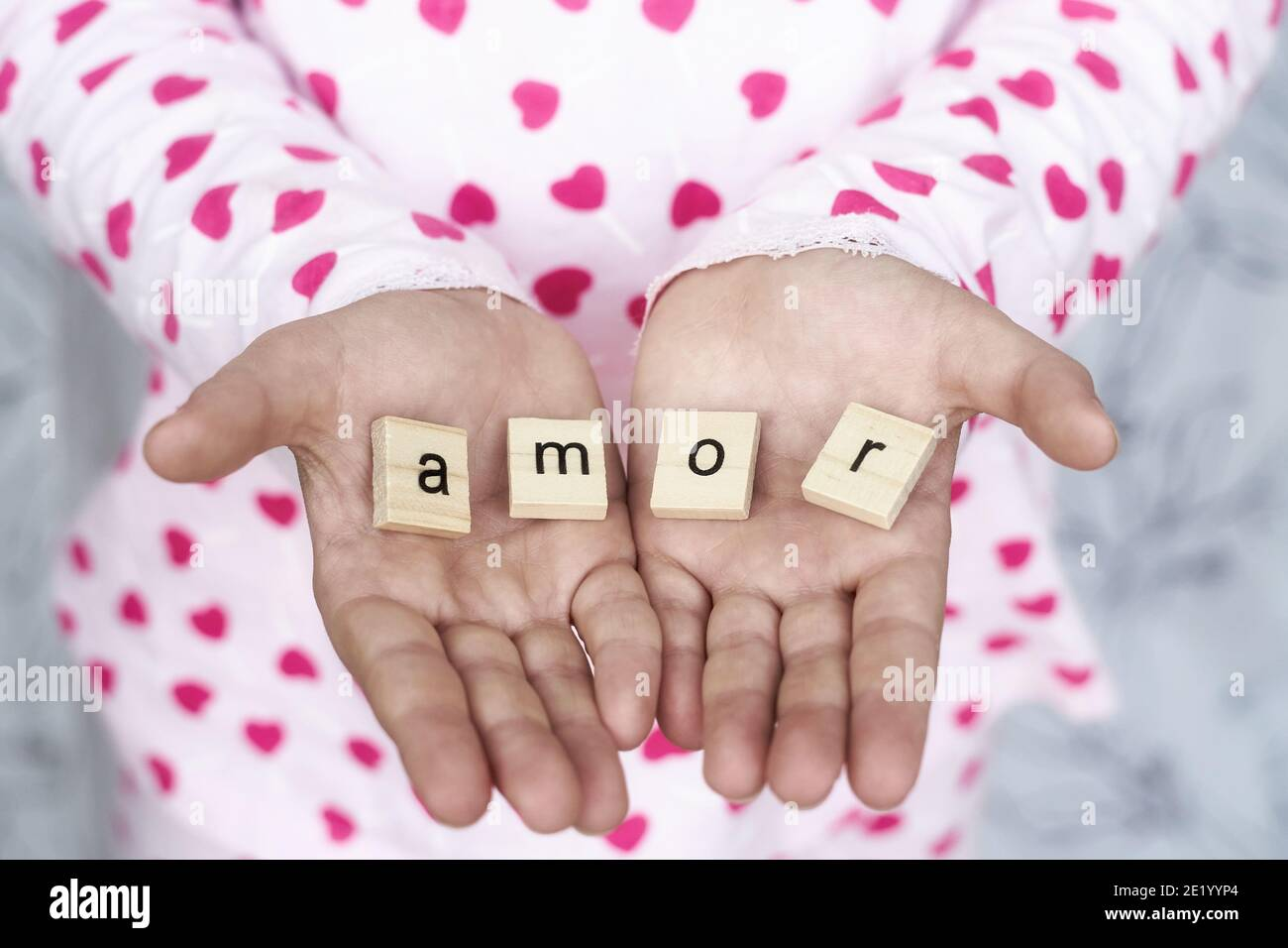 girl holds the word amor in her hands , selective focus Stock Photo