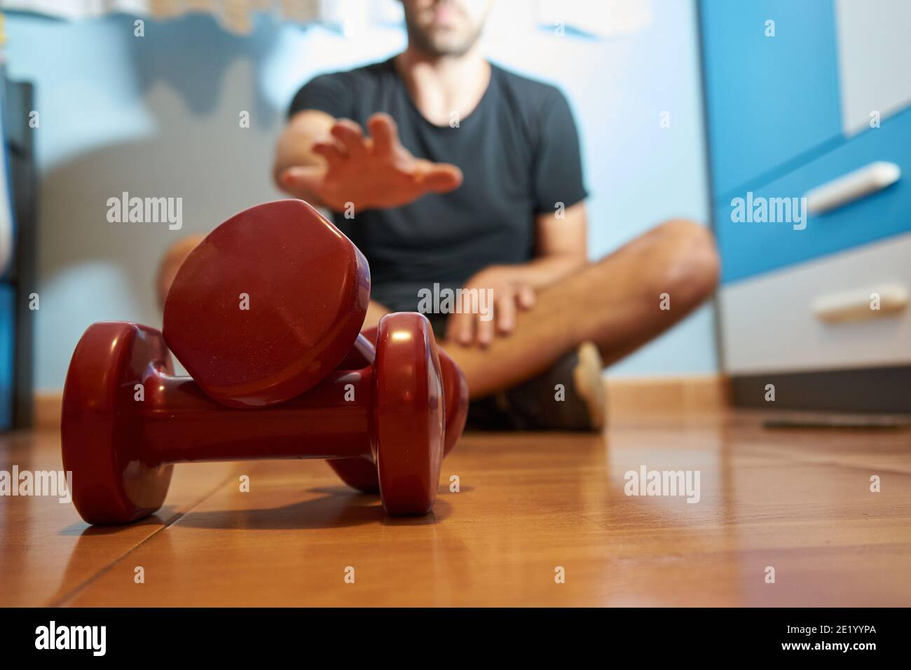 Man in his bedroom is going to do sport with weights, selective approach Stock Photo
