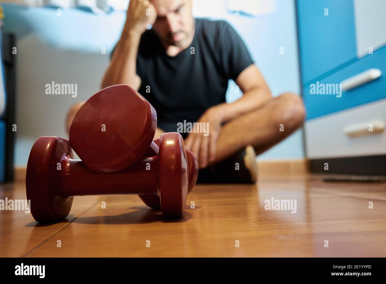 Man in his bedroom ready to do sport with weights, depressed or thinking state, selective approach Stock Photo
