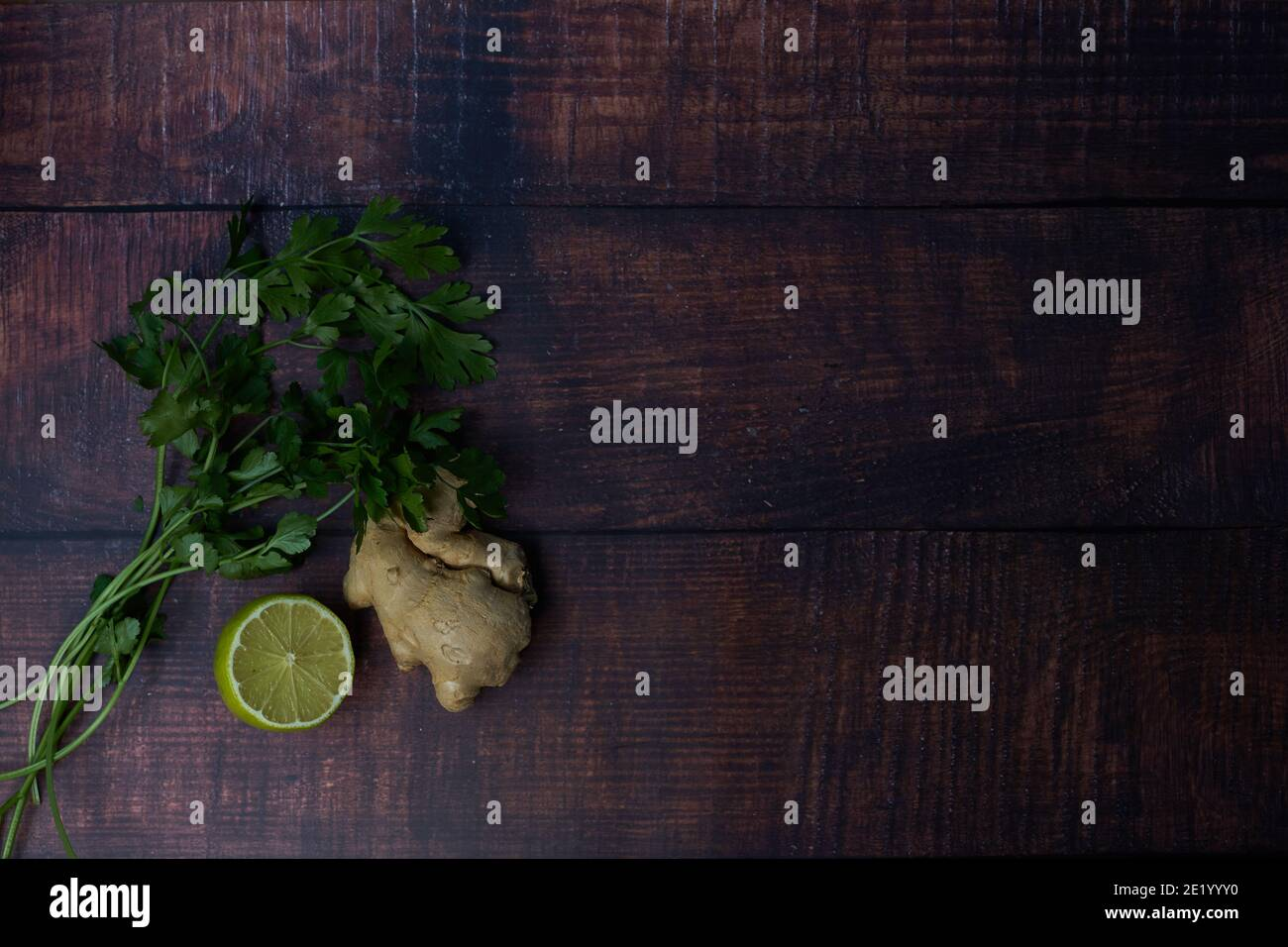 Fresh ingredients on wooden board. lime, coriander, parsley. Stock Photo