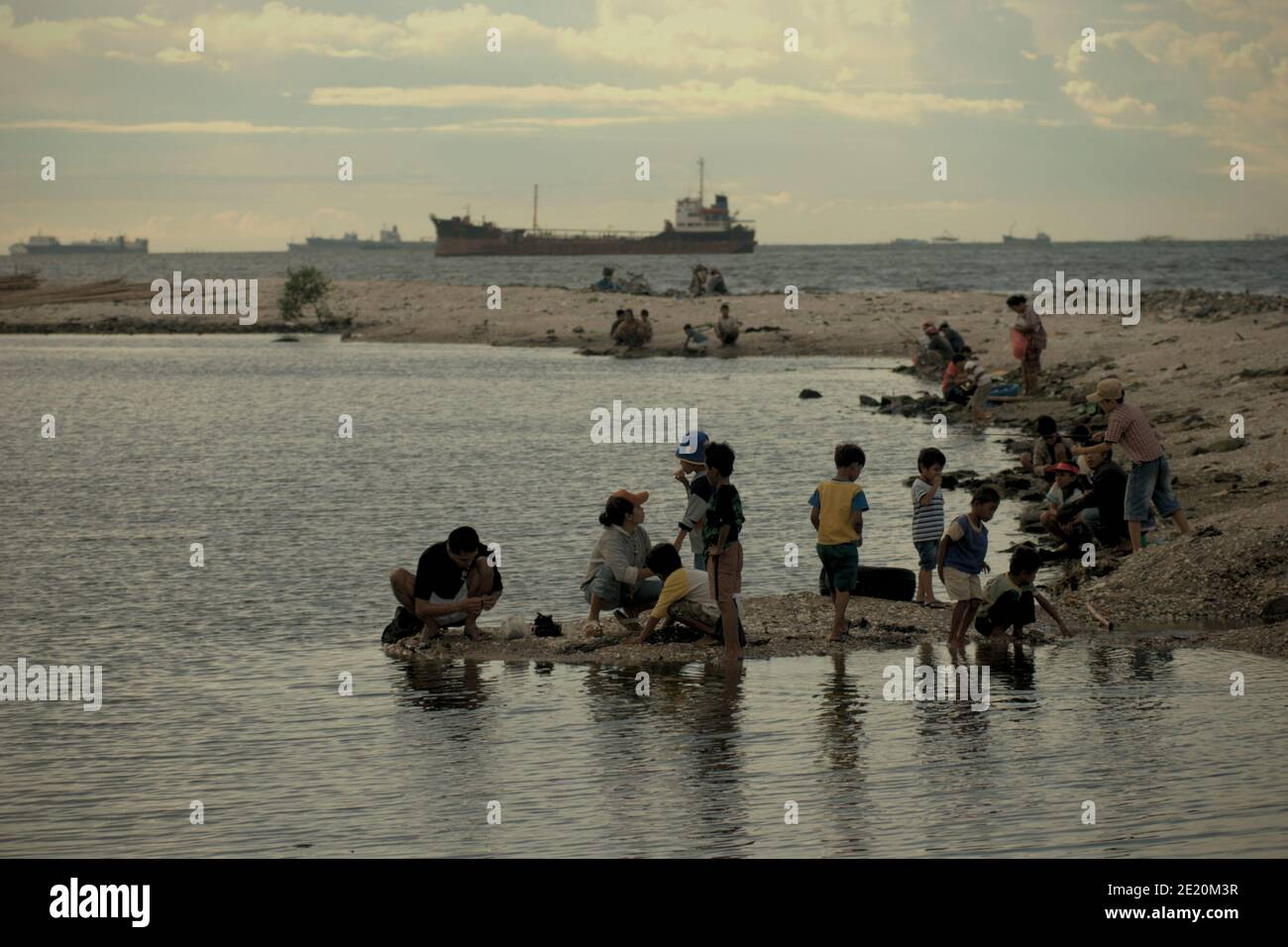 People having recreational time in Cilincing beach, on the coastal area of Jakarta, Indonesia. Port of Jakarta's traffics can be seen in the distance. Archival photo (2008). Stock Photo