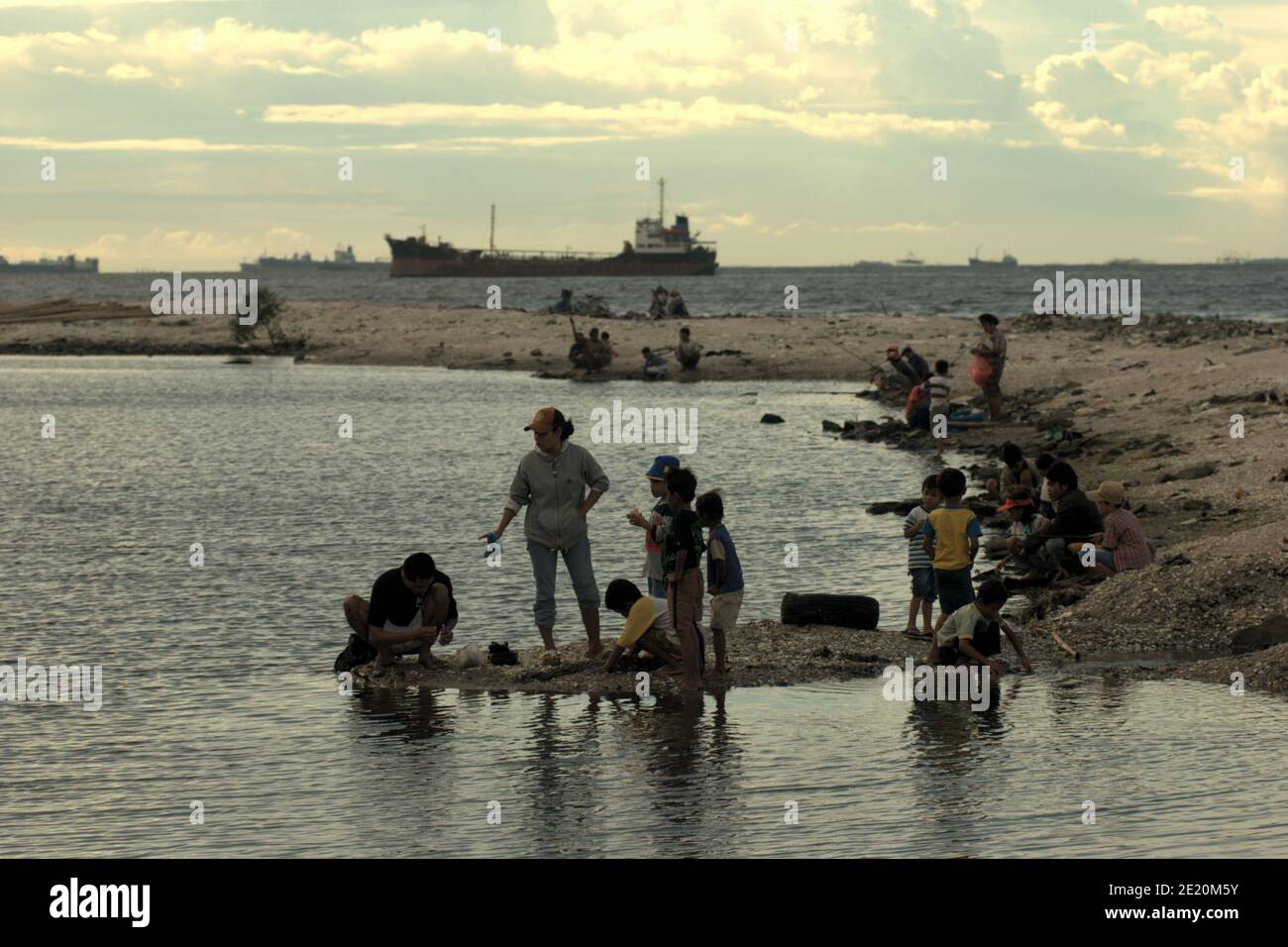 People having a recreational time on Cilincing beach in the coastal area of Jakarta, with a ship can be seen in the distance heading to the Port of Jakarta. Jakarta, Indonesia. Archival photo (2008). Stock Photo