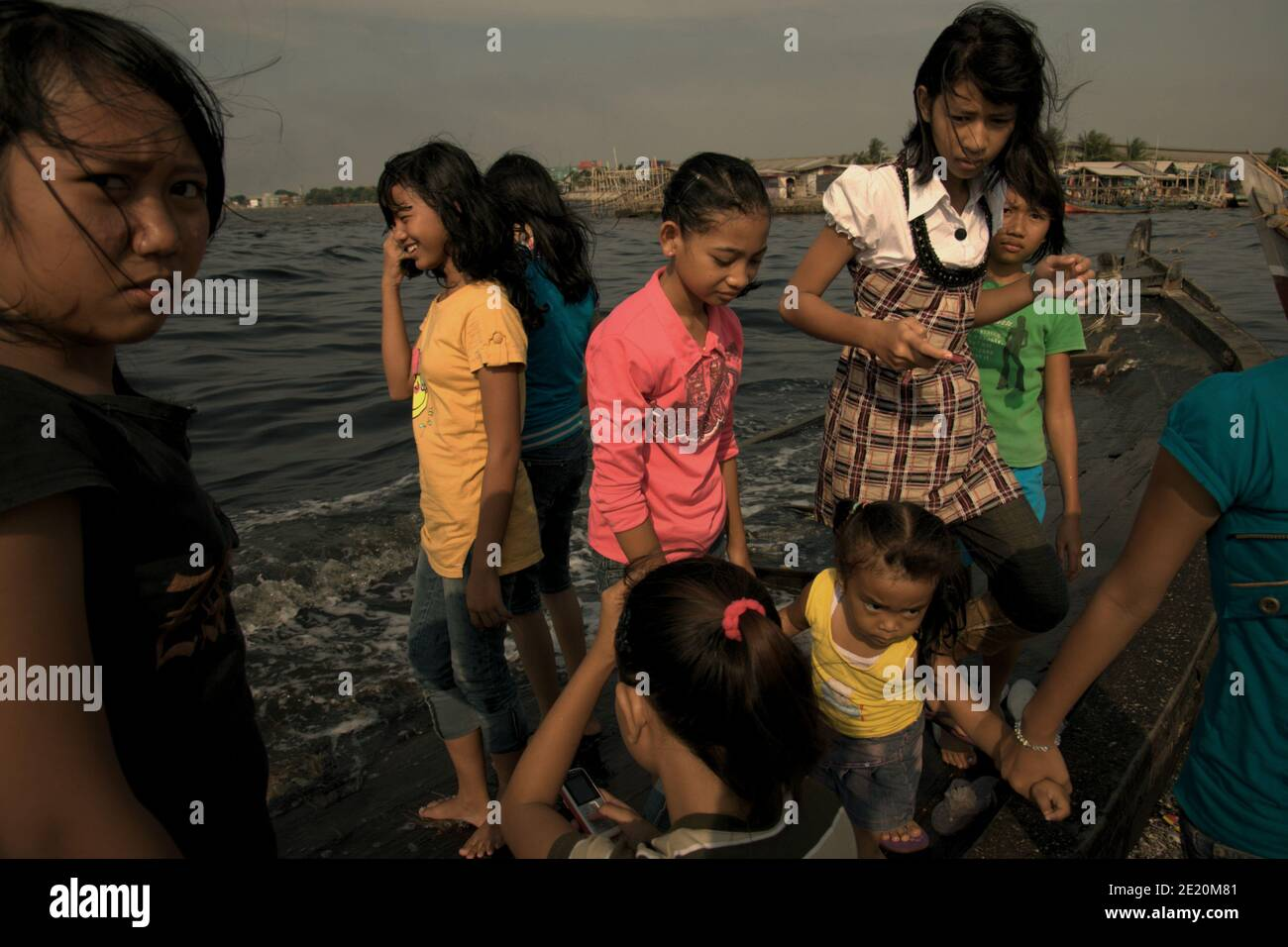 Teenagers having a leisure time on a broken boat tied to the beach in the fishing village of Cilincing, on the coastal area of Jakarta, Indonesia. Archival photo (2008). Stock Photo