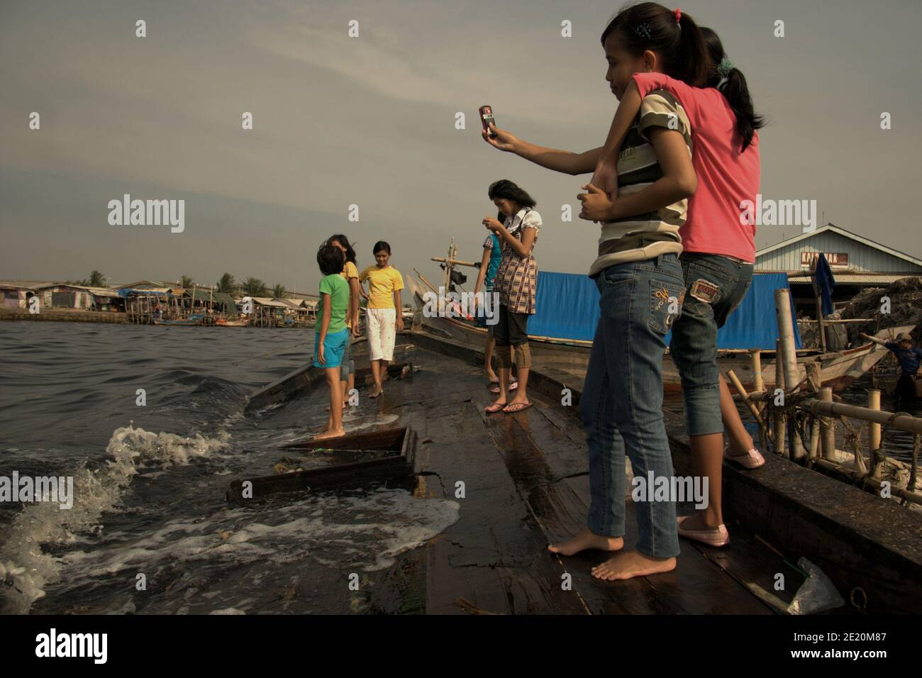 Teenagers taking selfie photo with mobile phone camera, as they are having a leisure time on a broken boat tied to the beach in the fishing village of Cilincing, on the coastal area of Jakarta, Indonesia. Archival photo (2008). © Reynold Sumayku Stock Photo