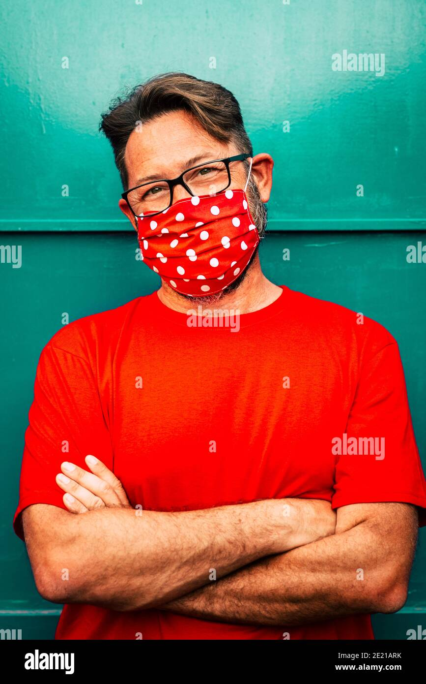 Coronavirus- covid-19 protection - Portrait of handsome adult people man wearing medical protection trendy mask in red color as t-shirt - green wall i Stock Photo