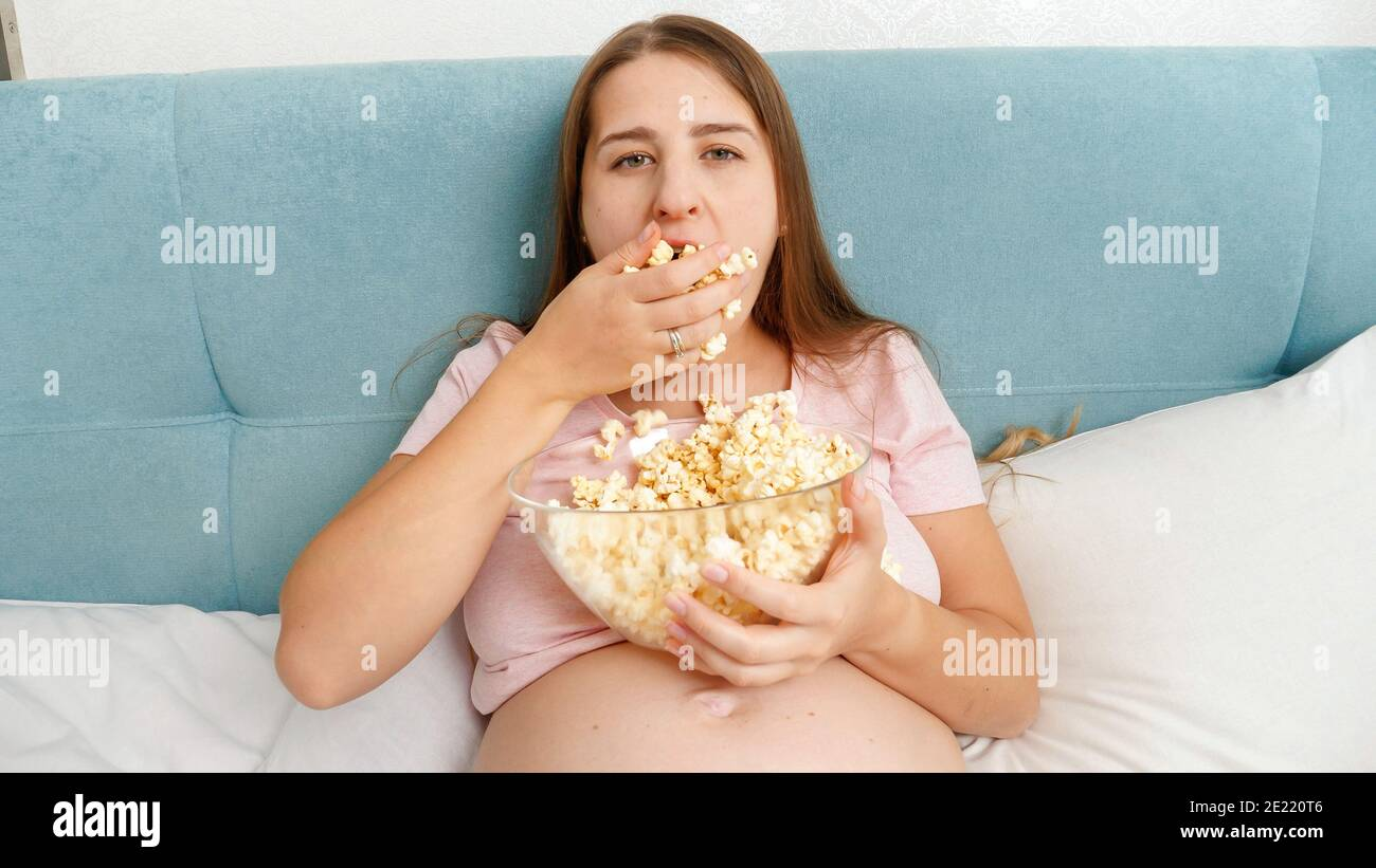 Pergnant woman feeling very hungry grabing handful of popcorn and putting it in mouth. Stock Photo