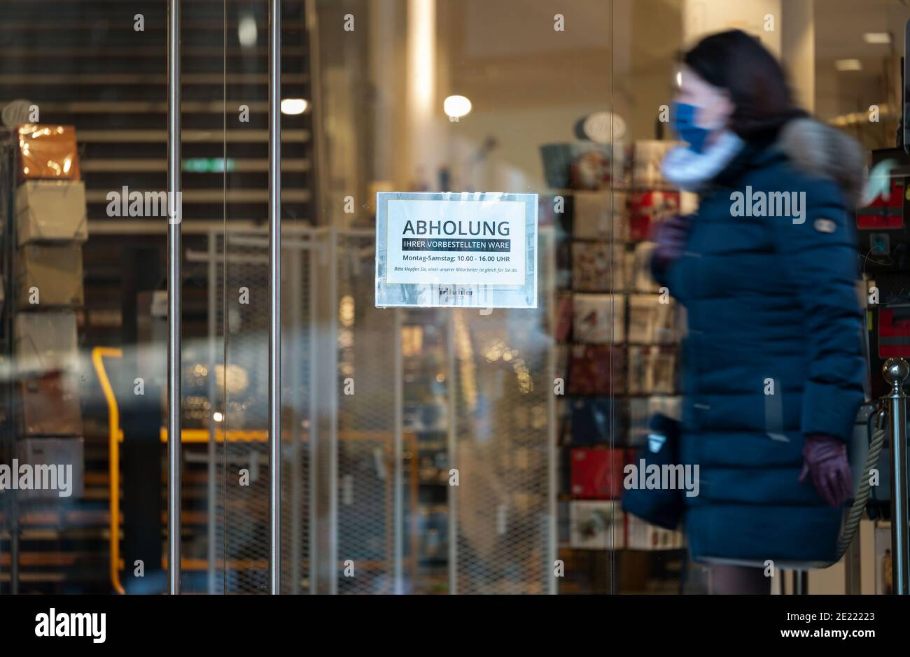 "11 January 2021, Baden-Wuerttemberg, Stuttgart: A sign with the inscription ""Abholung"" (pick-up) hangs at the entrance of the household goods store Tritschler. Since 11 January, the vast majority of businesses in the southwest are once again allowed to have their goods collected on site by customers if their orders have previously been placed by telephone or online, for example. Photo: Marijan Murat/dpa Stock Photo"