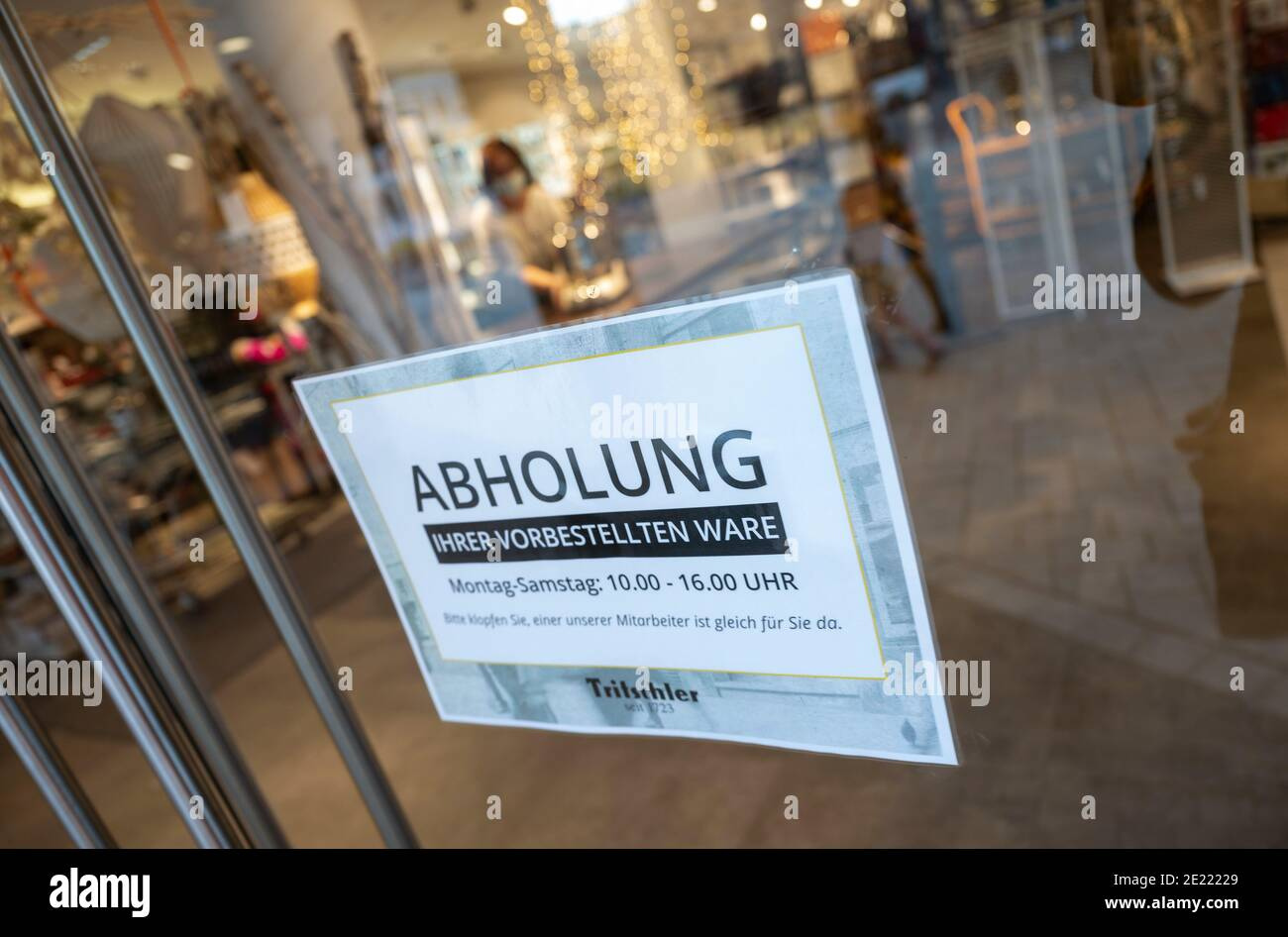 """11 January 2021, Baden-Wuerttemberg, Stuttgart: A sign with the inscription """"Abholung"""" (pick-up) hangs at the entrance of the household goods store Tritschler. Since 11 January, the vast majority of businesses in the southwest are once again allowed to have their goods collected on site by customers if their orders have previously been placed by telephone or online, for example. Photo: Marijan Murat/dpa Stock Photo"""