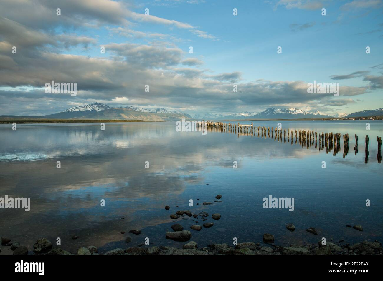Old wooden jetty reflected in waters of the Ultima Esperanze Sound / Golfo Almirante Montt Puerto Natales, Patagonia, Chile, Andes & Torres del Paine Stock Photo