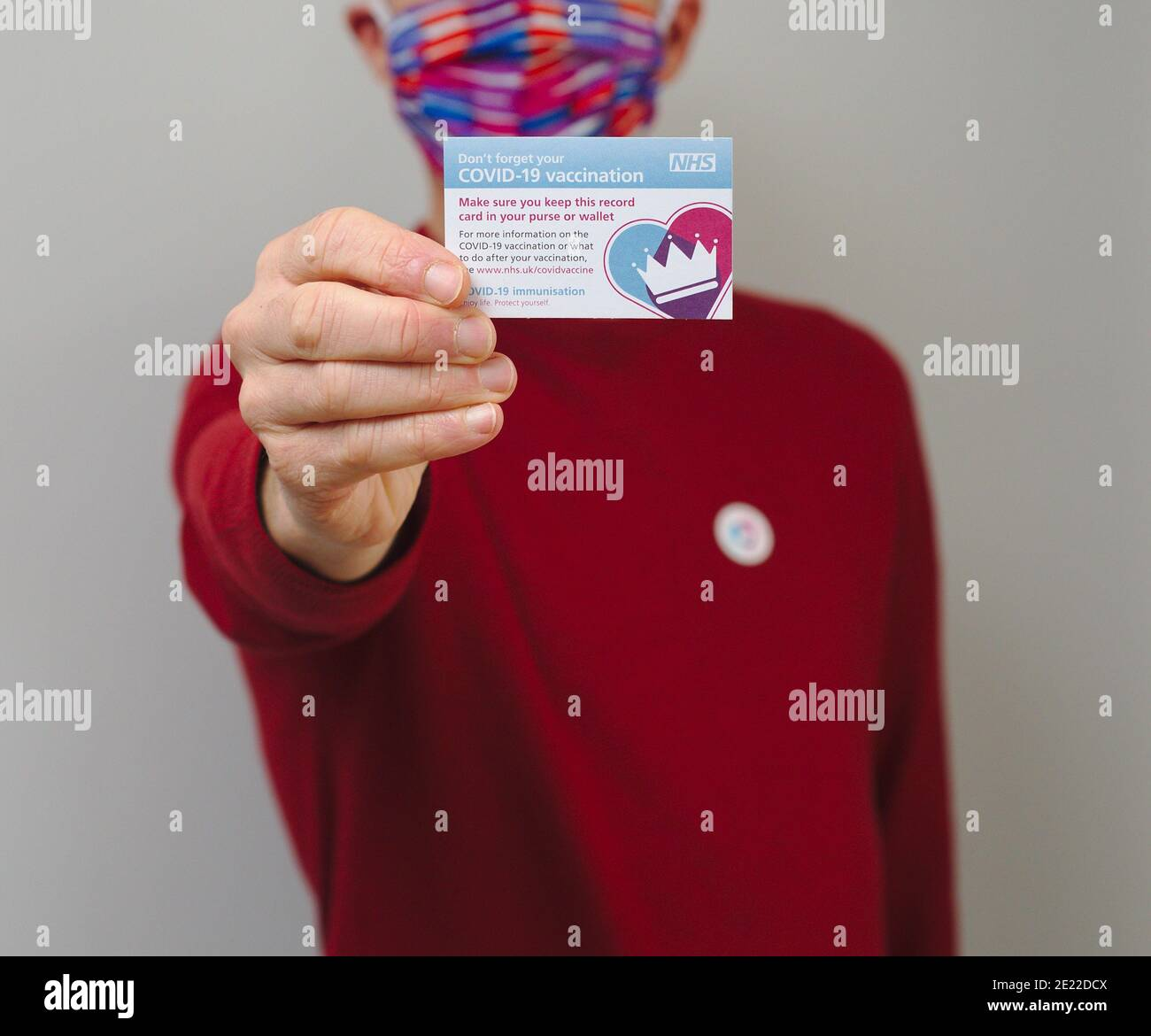 Vaccinated man wearing face mask and holding NHS Covid 19 vaccination record card Stock Photo