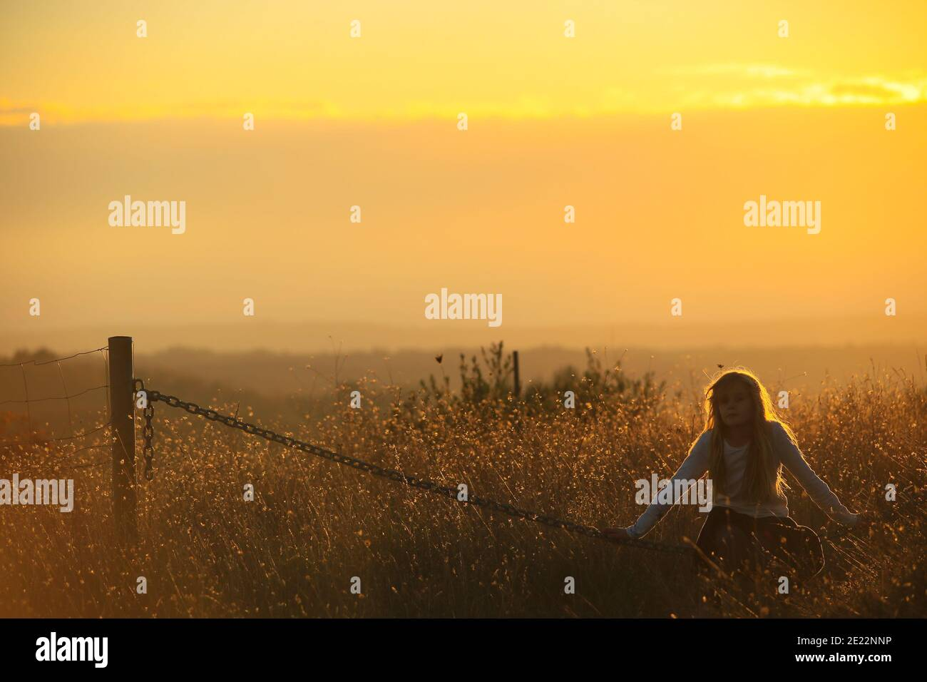 Young Blonde girl sits on a chain in a golden sunset Stock Photo