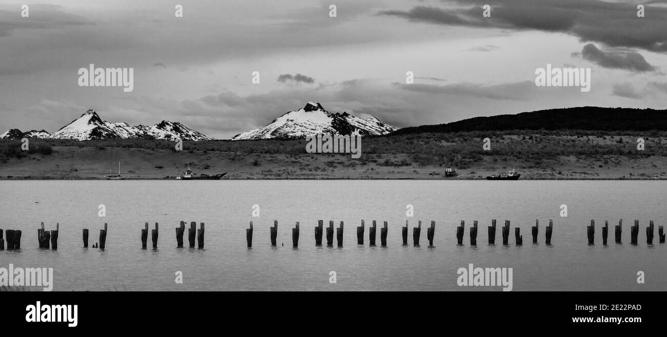 Black and white image of old jetty with the Andes mountains in the distance at Puerto Natales, Patagonia, Chile, South America Stock Photo