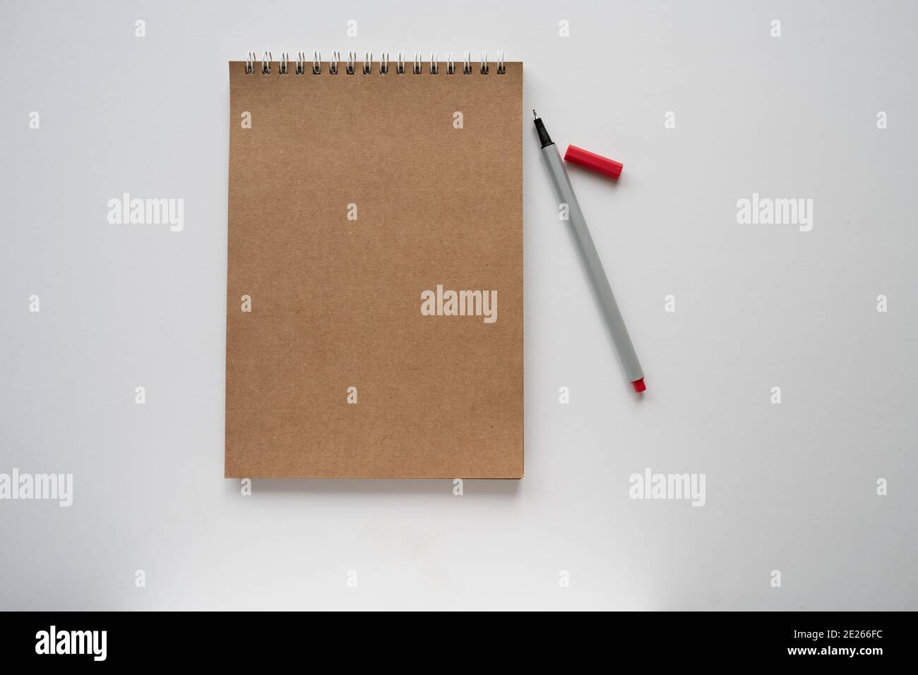 craft papper notebook and red pencil on white background, isolated. taking note. new year's resolution, goals. Stock Photo