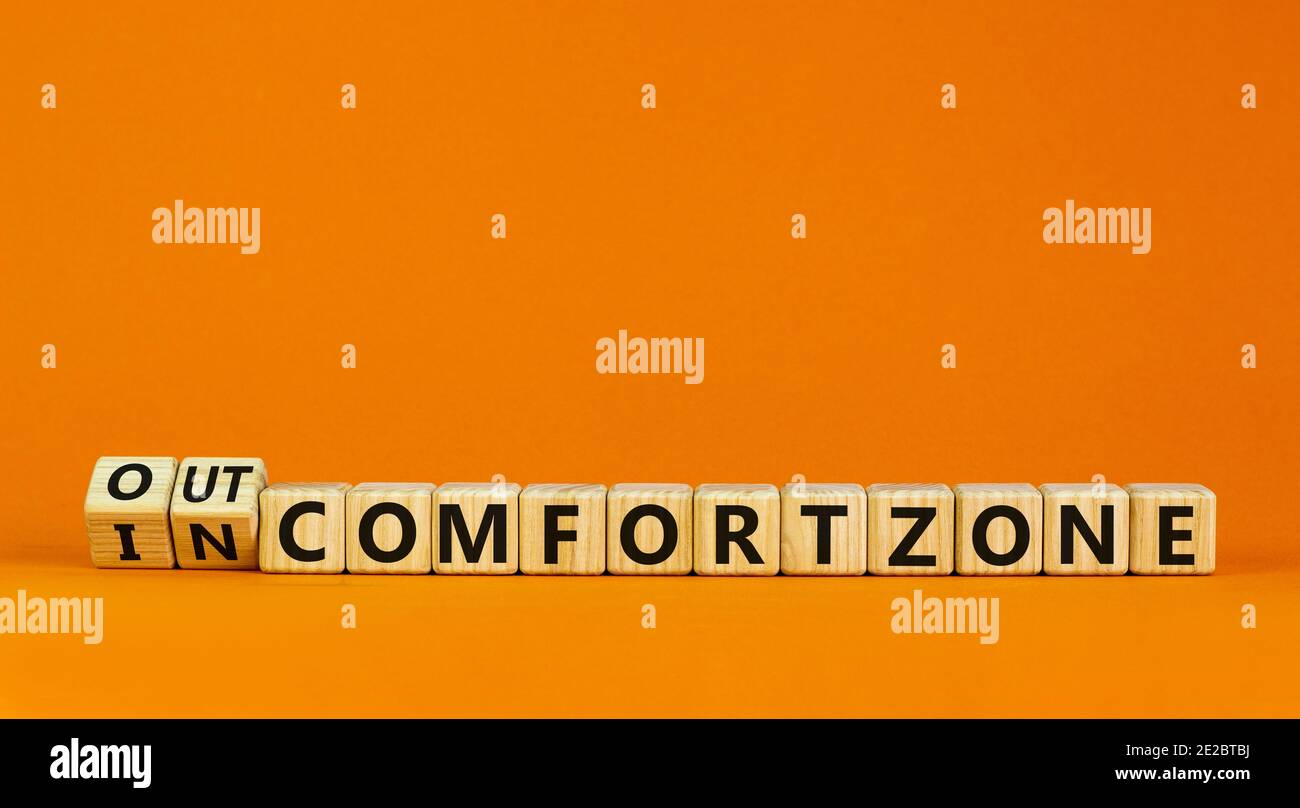 Out or in comfort zone symbol. Turned wooden cubes and changed words 'in comfort zone' to 'out comfort zone'. Beautiful orange background, copy space. Stock Photo