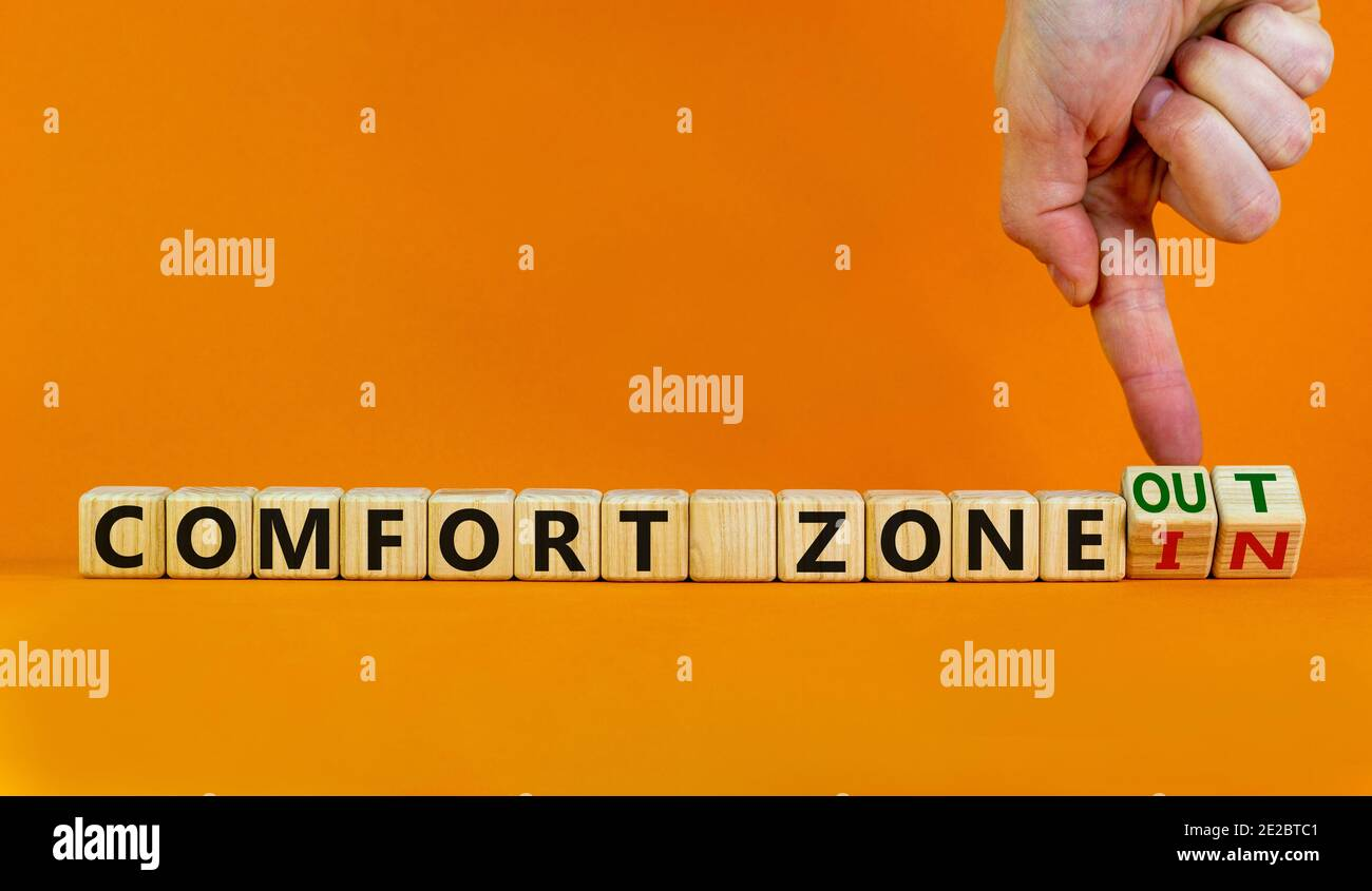 Out or in comfort zone symbol. Hand turns wooden cubes and changes words 'in comfort zone' to 'out comfort zone'. Beautiful orange background, copy sp Stock Photo