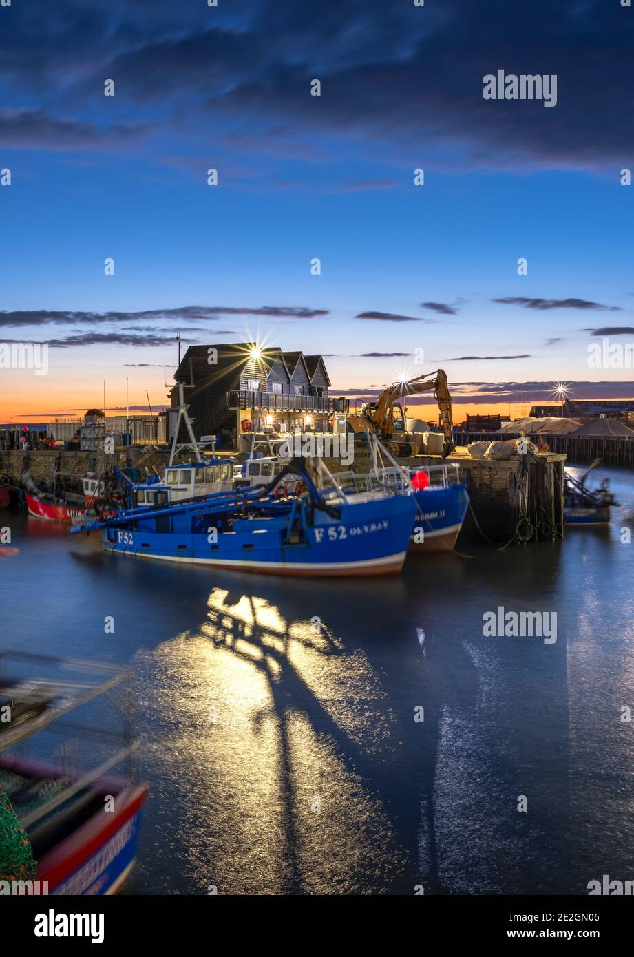Fishing vessels in Whitstable harbour illuminated at dusk on the North Kent coast. Stock Photo