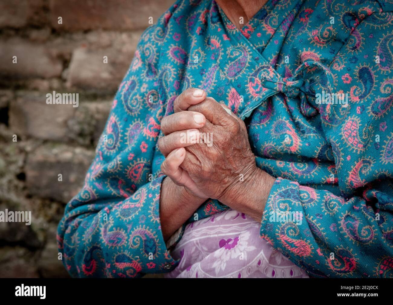 Unrecognized elder woman wearing blue cloths crossing her wrinkled hands. Aging age process Stock Photo