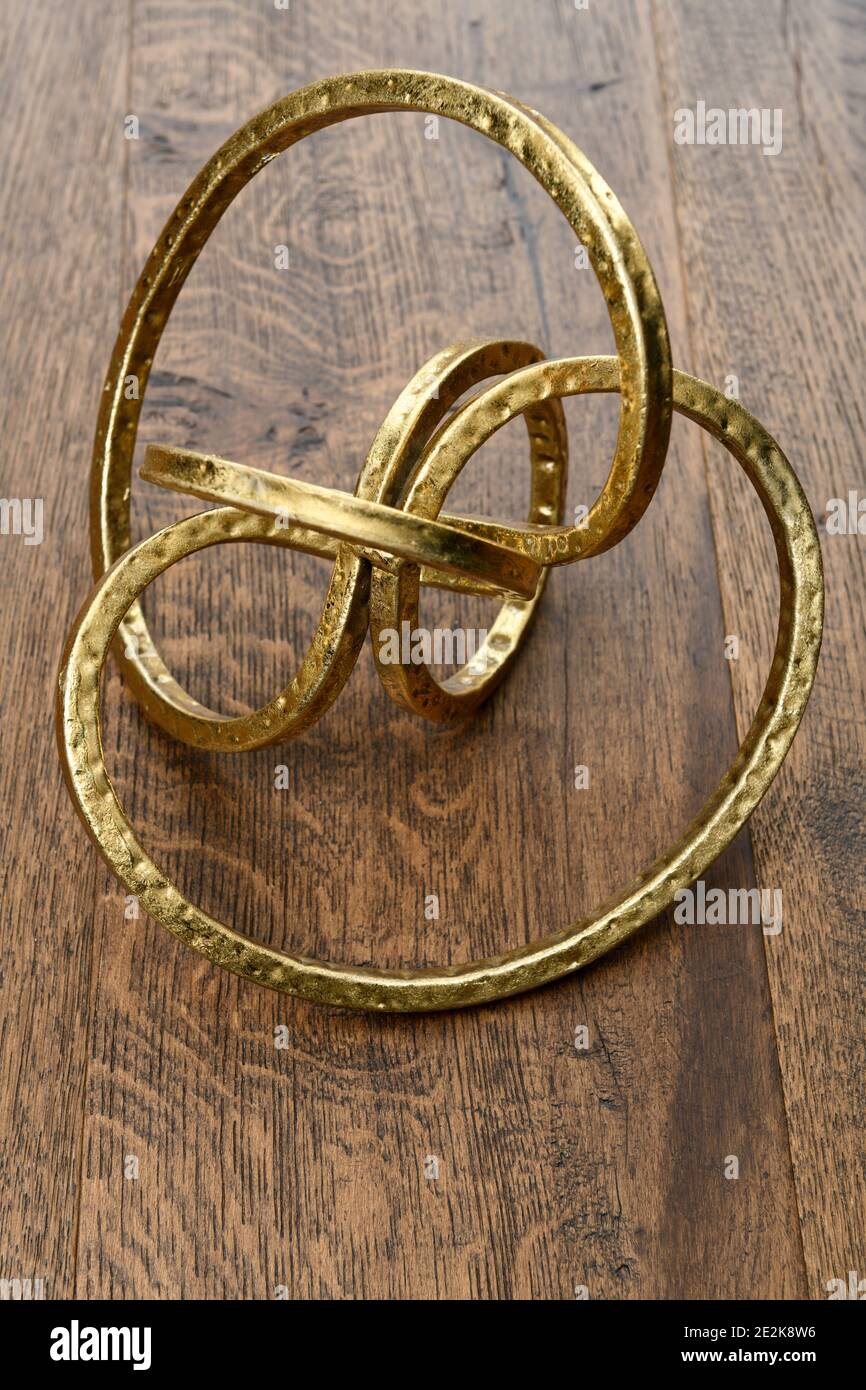 Gold metal torus infinity shape on dark hickory wood Stock Photo