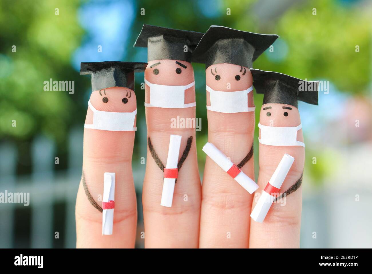 Fingers art of students in medical mask from COVID-2019. Graduates holding their diploma after graduation. Stock Photo
