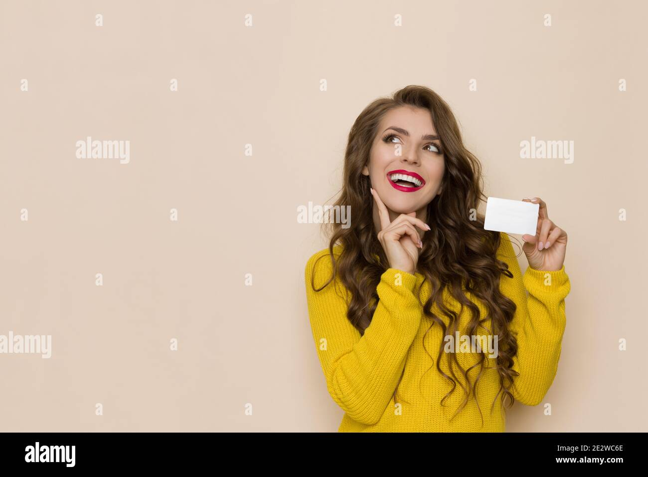 Casual young woman is holding white plastic card, smiling, looking up and thinking. Waist up studio shot on beige background. Stock Photo