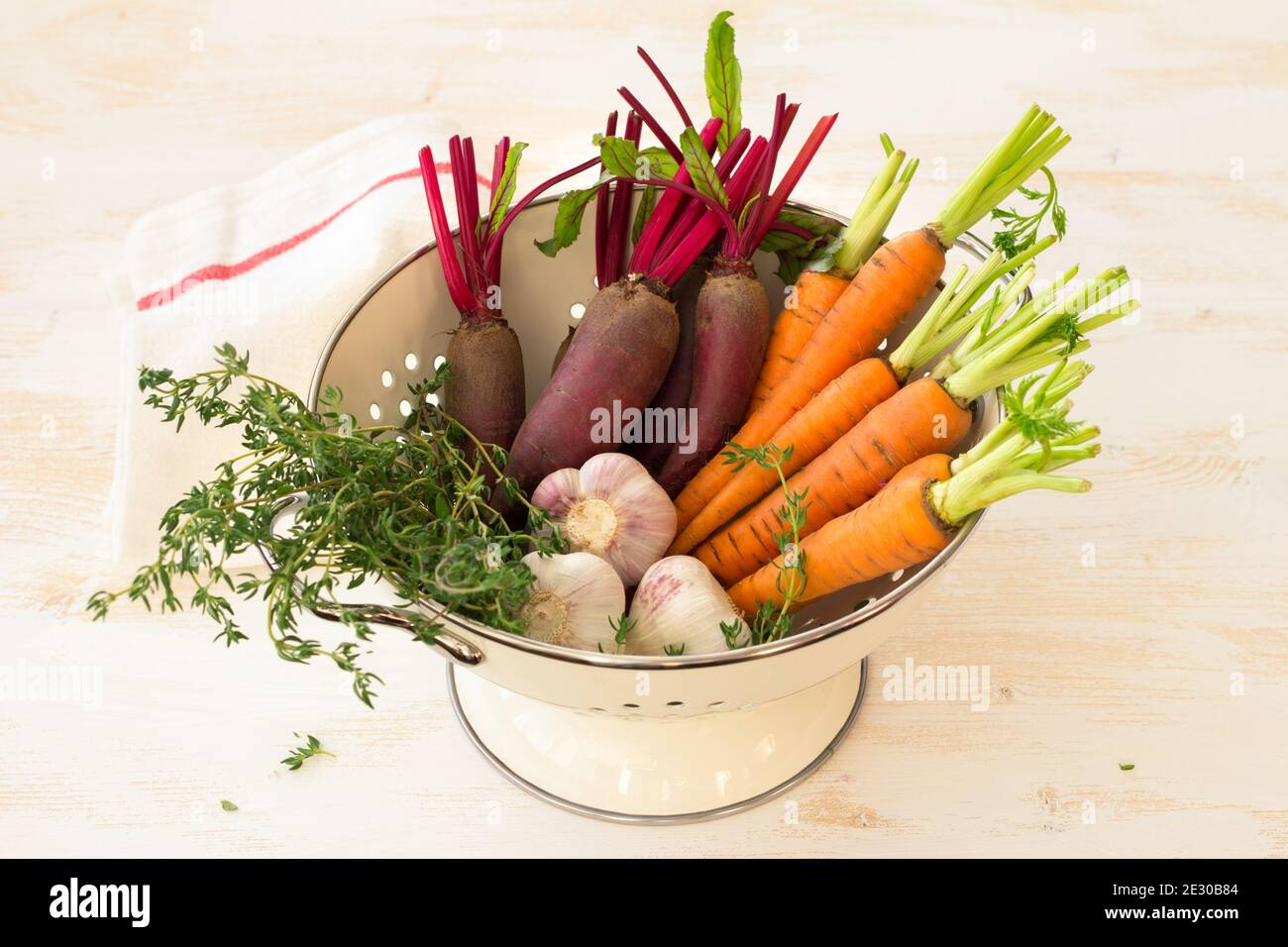 Fresh young organic vegetables, carrots, beets, garlic and greens for salad in colander on white background, selective focus. Healthy vegan food Stock Photo
