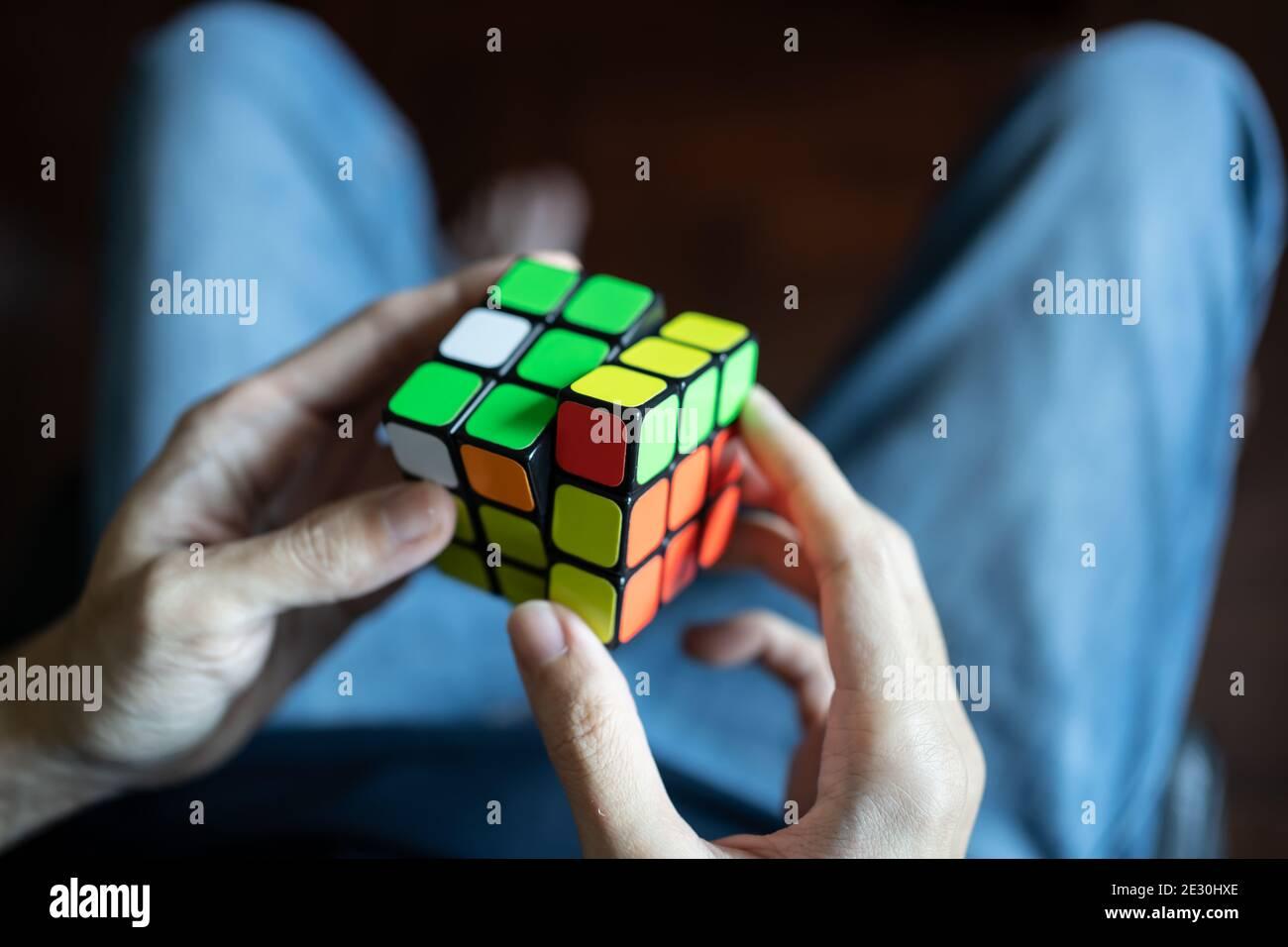 Bangkok, Thailand - January 13, 2021 : A man solving Rubik's cube. Stock Photo