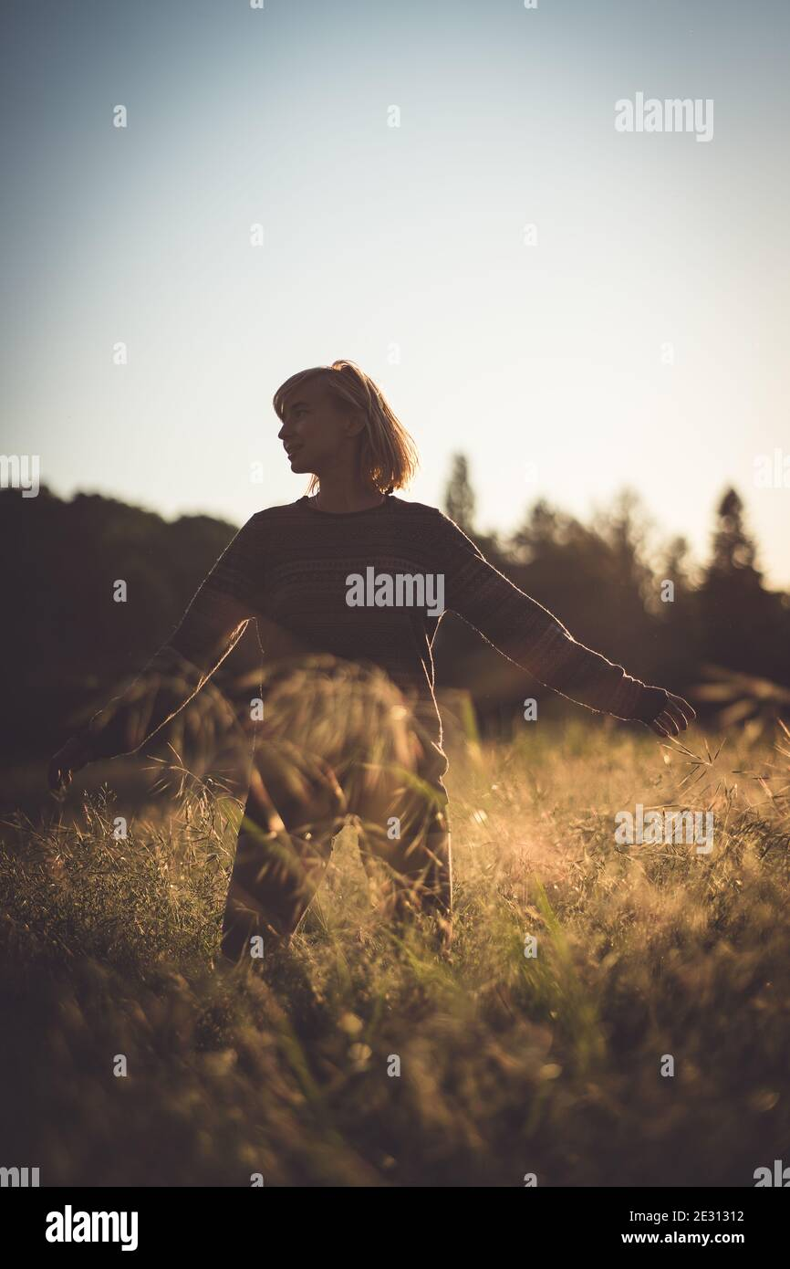 A young woman dancing in tall grass during golden hour Stock Photo