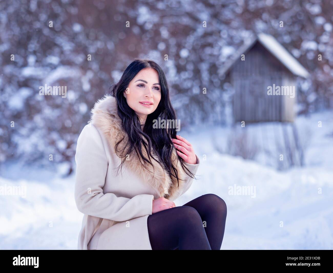Young woman in nature countryside snow during Winter season daydreaming looking away serious wait waiting dreamy exposed exposing knees legs Stock Photo