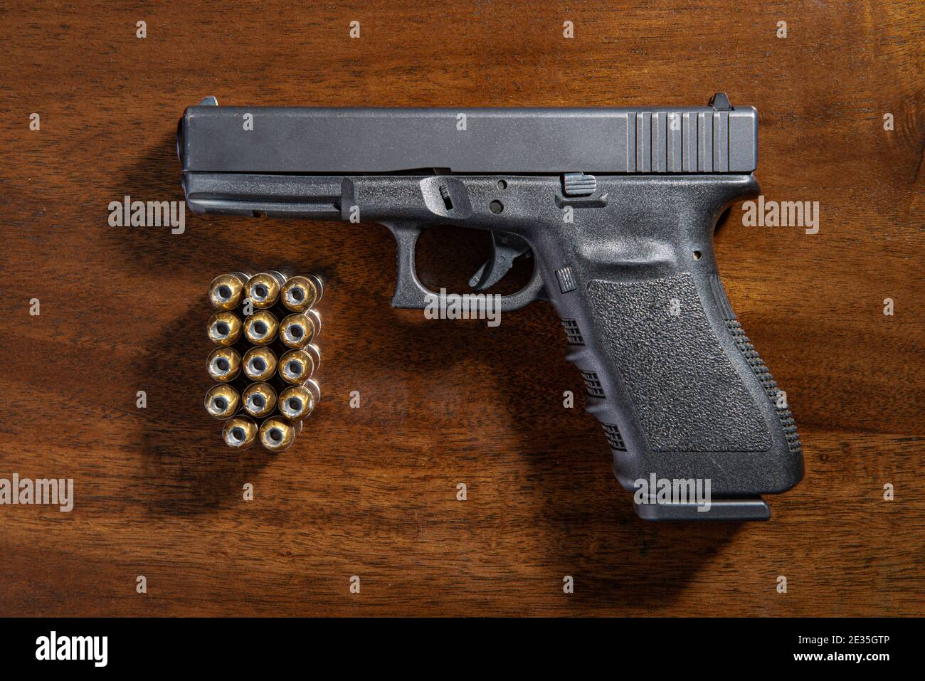 A black semi-automatic pistol and ammunition on a wooden table. Stock Photo
