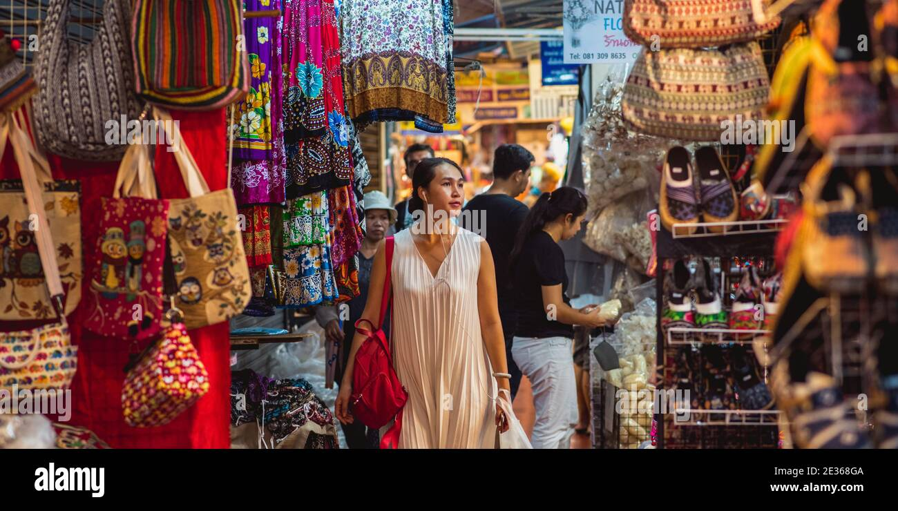 Bangkok, Thailand - May 14, 2017: Young Asian woman (unidentified) walks with headphones along stalls and stands of Chatuchak market. Stock Photo