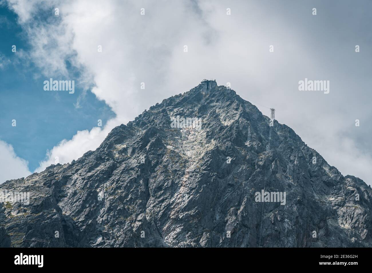 View of the Lomnicky stit peak, famous rocky summit in High Tatras, Slovakia. Cloudy windy day. Stock Photo