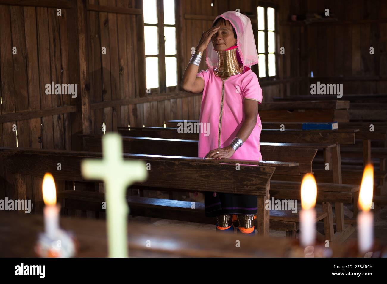Myanmar, Loikaw, Panpet: Woman of Kayan Lahwi tribe praying in an old wooden church. Stock Photo