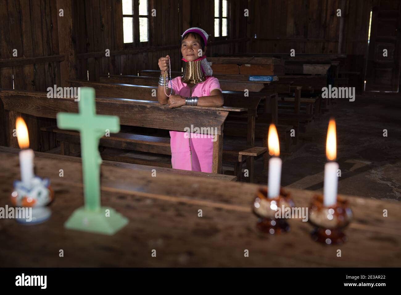 Myanmar, Loikaw, Panpet: Woman of Kayan Lahwi tribe praying the rosary in an old wooden church. Stock Photo